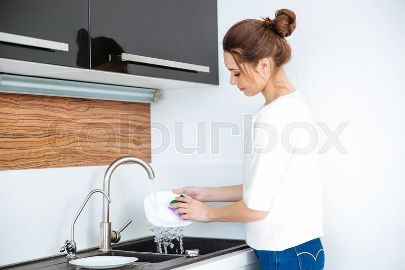 Cute lovely young woman standing and washing dishes at home, stock photo