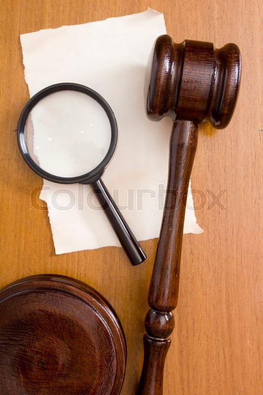 Stock image of 'The surface of the table with the judge's hammer and a magnifying glass.'