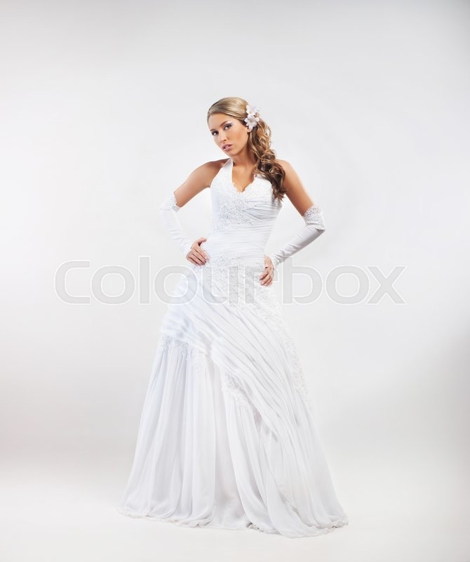 Stock image of 'Full-length portrait of gorgeous bride wearing wedding dress and flower alike accessories over grey background.'