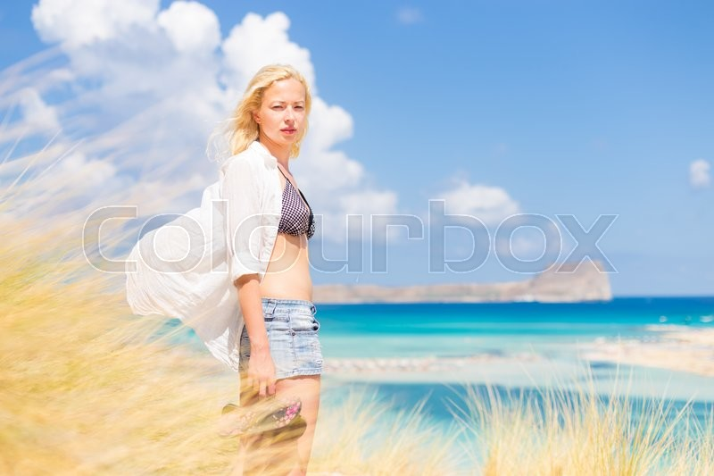 Stock image of 'Relaxed woman enjoying freedom and life an a beautiful sandy beach.  Young lady feeling free, relaxed and happy. Concept of freedom, happiness, enjoyment and well being.  Enjoying Sun on Vacations.'