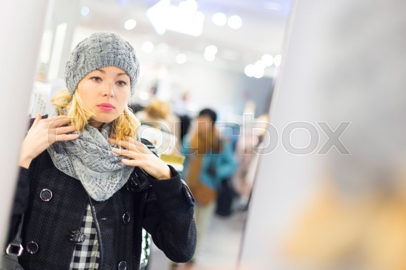 Stock image of 'Woman shopping clothes. Shopper looking at clothing indoors in store. Beautiful blonde caucasian female model. '