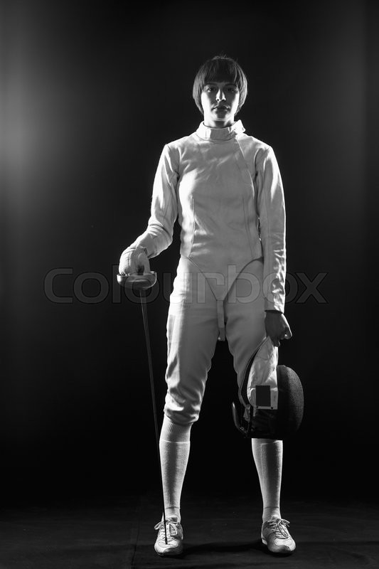Stock image of 'The portrait of woman wearing white fencing costume and black fencing mask  with the rapier on black background'