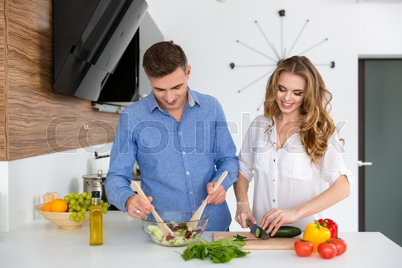 Stock image of 'Beautiful couple standing and cooking healthy food together on the kitchen'