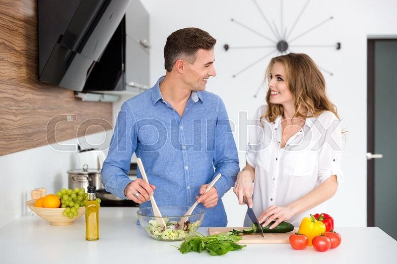 Stock image of 'Portrait of a happy beautiful couple cooking together on the kitchen '