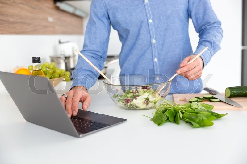 Stock image of 'Closeup of man in blue shirt using laptop and making salad in glass bowl on the kitchen'
