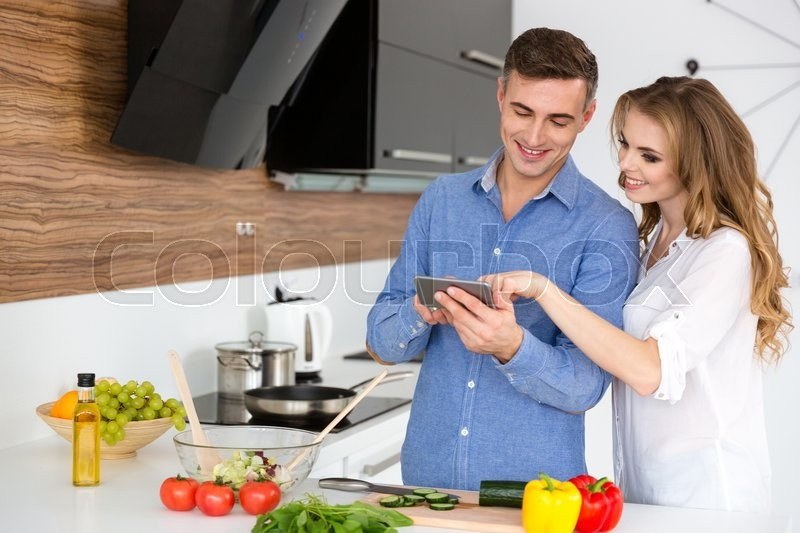 Stock image of 'Beautiful couple using smartphone and cooking on the kitchen at home'