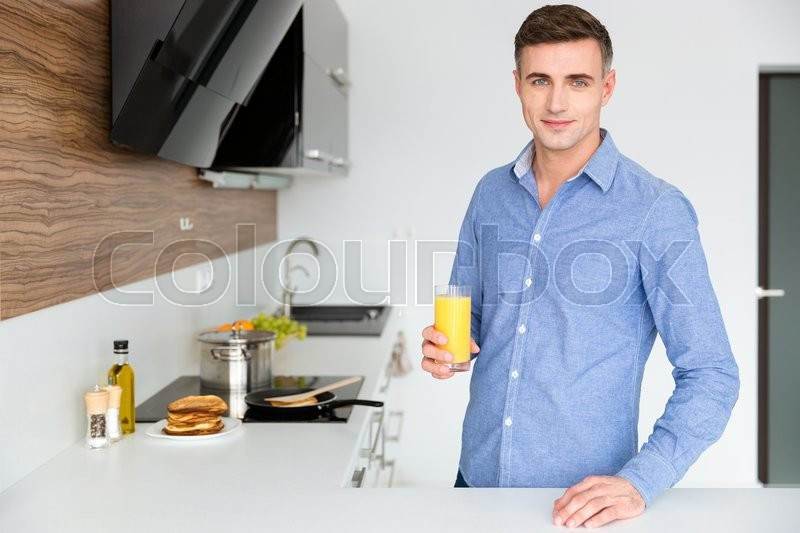 Stock image of 'Handsome man in blue shirt standing on the kitchen and drinking orange juice'