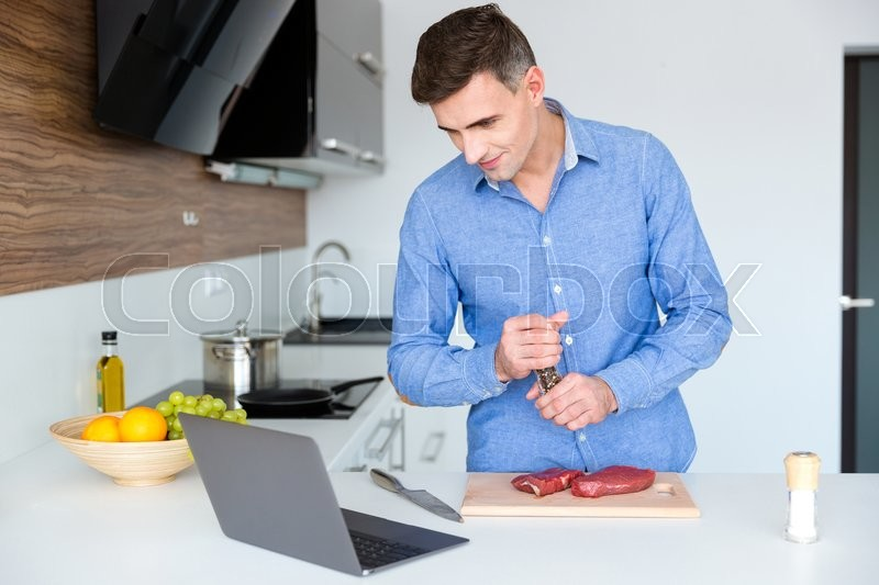 Stock image of 'Handsome male in blue shit watching cooking lesson on laptop and preparing meat on the kitchen'