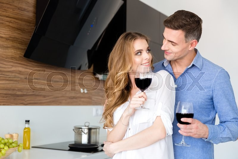 Stock image of 'Happy couple drinking red wine and flirting on the kitchen at home'