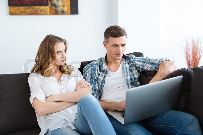 Stock image of 'Unhappy woman sitting on sofa with arms crossed while her husband working with laptop '