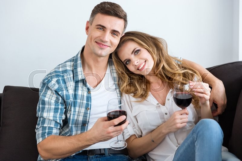 Stock image of 'Beaytiful couple sitting on sofa and drinking wine at home'