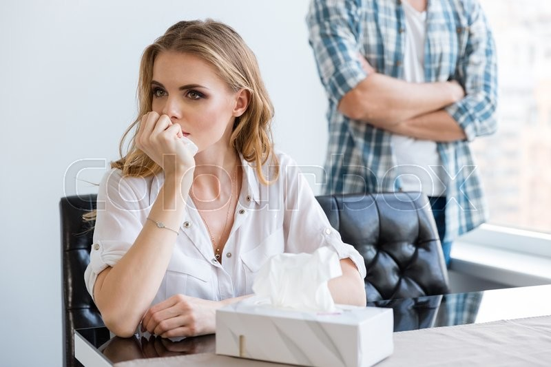 Stock image of 'Unhappy woman crying after quarrel with her husband at home'