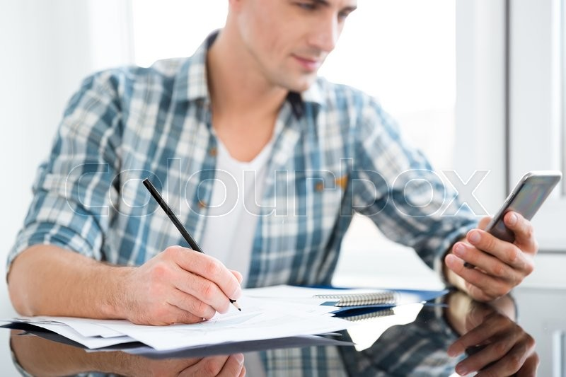 Stock image of 'Closeup of smartphone and documents used by serious man working at the table'