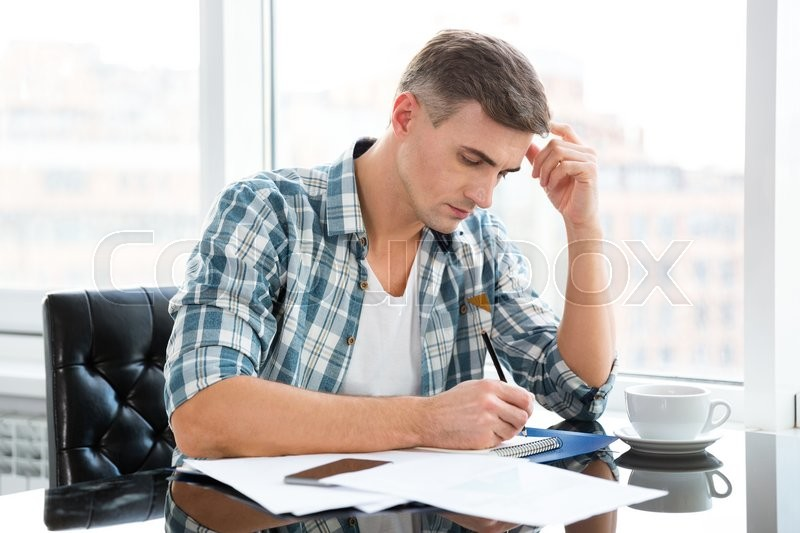 Stock image of 'Handsome thoughtful man in checkered shirt sitting at the table with bills '