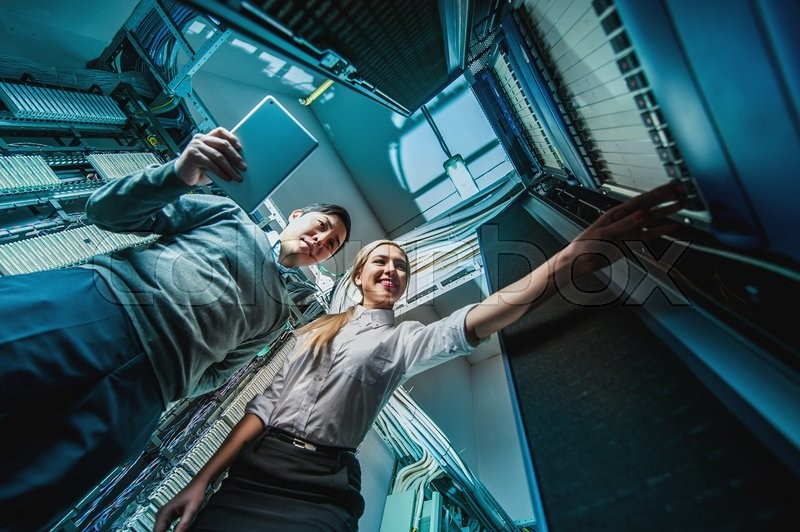 Stock image of 'Young engineers businessmen in network server room'