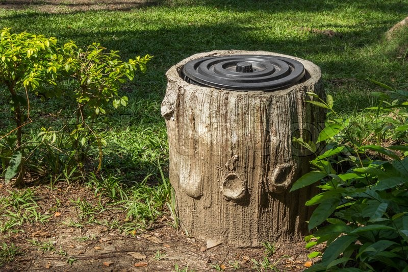 Stock image of 'Trash bin In The Park With Tree Trunk Design.'