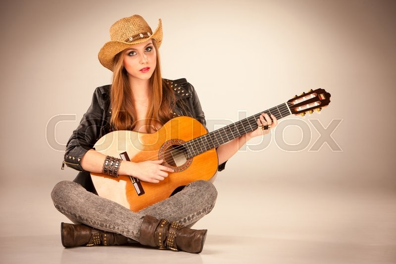Stock image of 'The beautiful girl in a cowboy's hat  and acoustic guitar on a gray background'