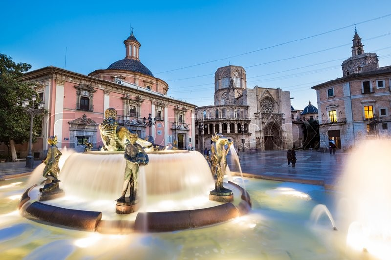 Stock image of 'Square of Saint Mary's, fountain Rio Turia and cathedral in background at dusk in Valencia, Spain.'