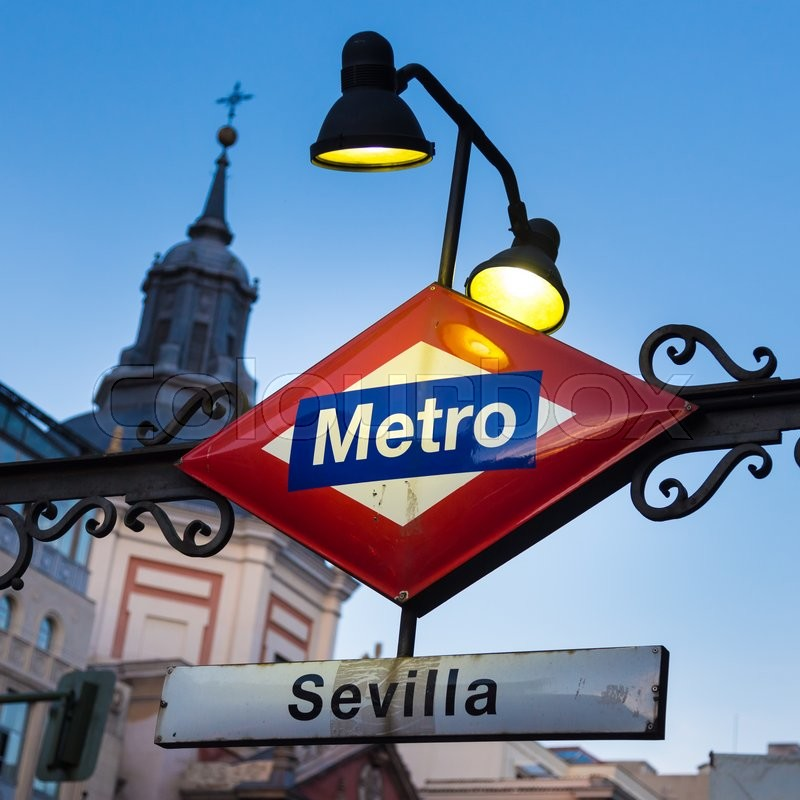 Stock image of 'Detail of Vintage Sevilla Metro Station Sign in Madrid Spain, illuminated in dusk.'