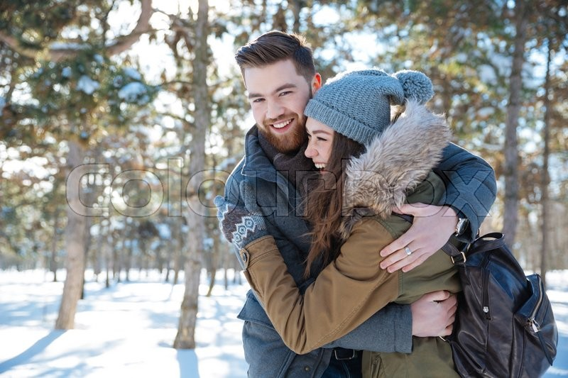 Stock image of 'Smiling young couple hugging in winter park'