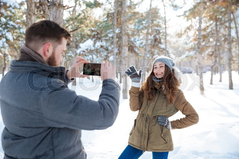 Stock image of 'Man making photo of his girlfriend on smartphone in winter park'