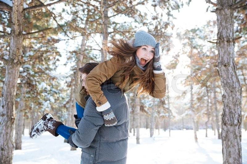 Stock image of 'Man carrying cheerful woman on his shoulders in winter park'