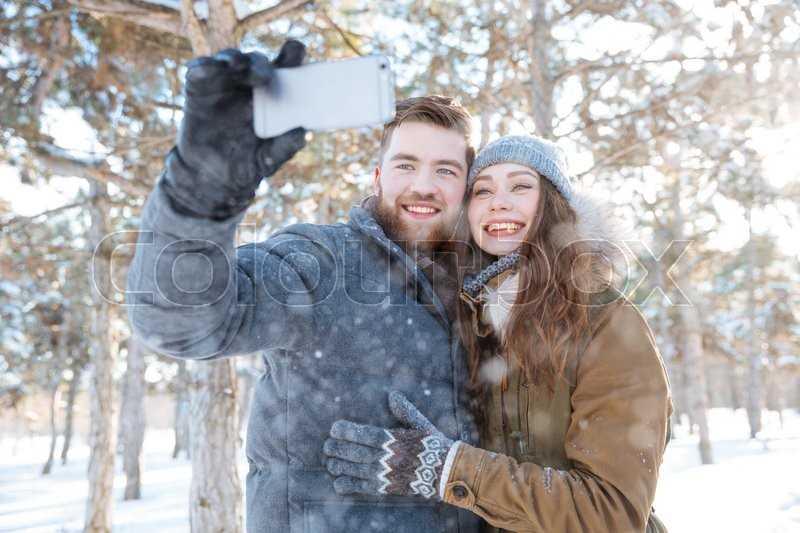 Stock image of 'Smiling couple making photo on smartphone in winter park'