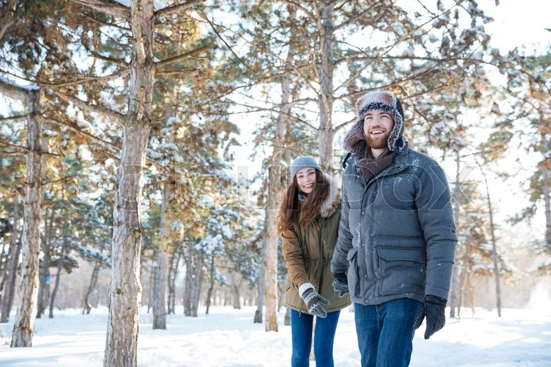 Stock image of 'Beautiful happy couple in winter clothes walking outdoors in park'