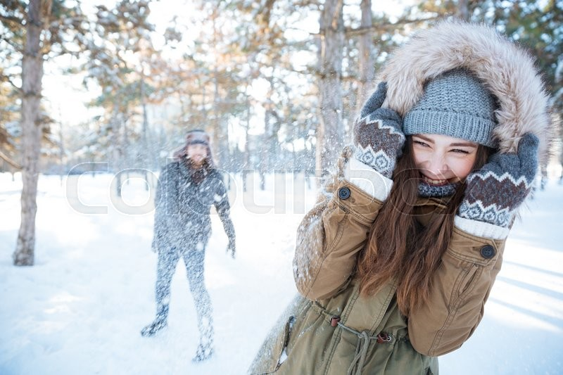 Stock image of 'Happy young couple in winter clothes playing snowballs outdoors'