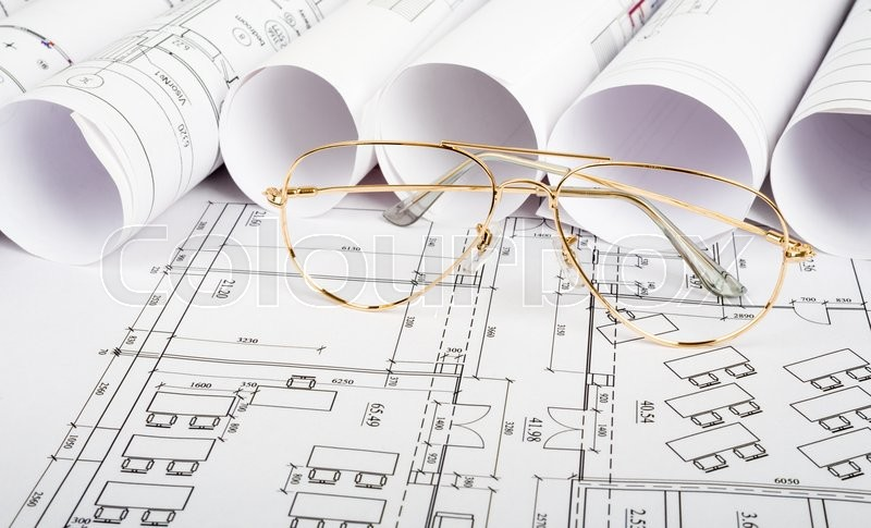 Stock image of 'Glasses on blueprint and blueprint rolls background'