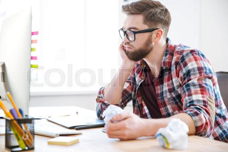 Stock image of 'Handsome man thinking and crumpling paper on his workplace'