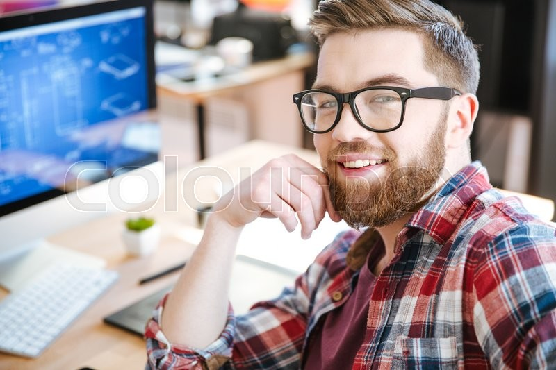 Stock image of 'Happy attractive young man with beard in glasses working and designing project on his computer '