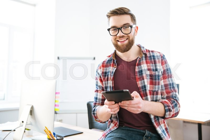 Stock image of 'Cheerful attractive young male with beard in checkered shirt and glasses using tablet in the office'