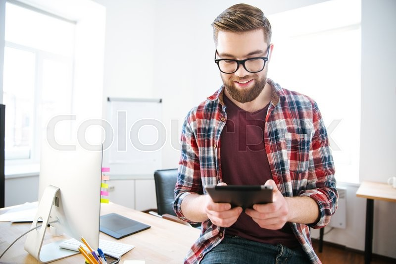 Stock image of 'Happy handsome man with beard in plaid shirt and glasses sitting on the table in office and using tablet'