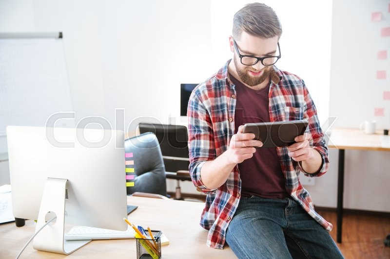 Stock image of 'Portrait of smiling young bearded man sitting with tablet on the table in office'