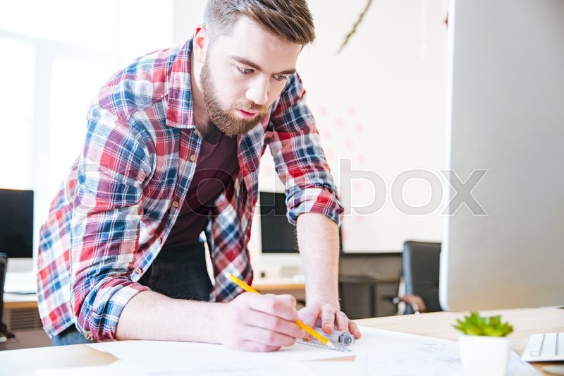 Stock image of 'Concentrated handsome man in checkered shirt working and drawing blueprint with ruler and pencil'