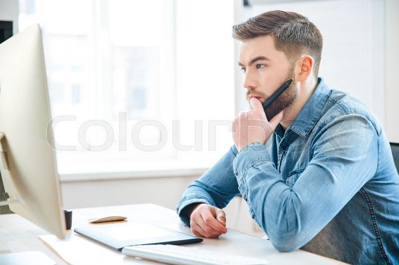 Stock image of 'Pensive attractive bearded male designer in jeans shirt thinking and making blueprints using pen tablet '
