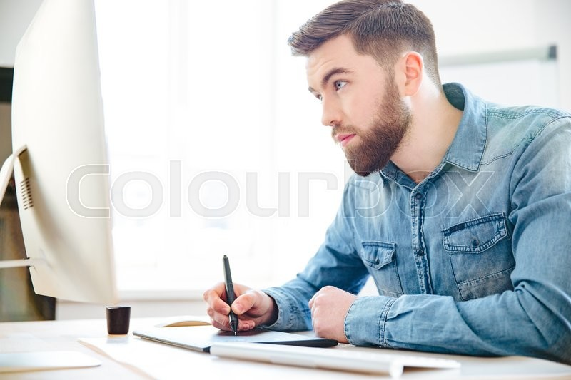 Stock image of 'Concentrated handsome young designer with beard in blue shirt drawing using computer and graphic tablet in the office'