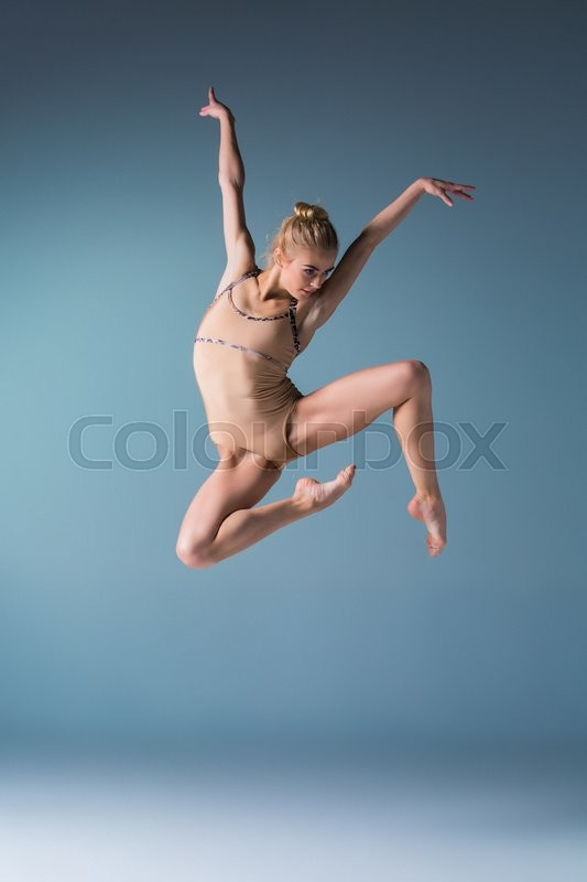 Stock image of 'young beautiful modern style dancer jumping on a studio blue background'