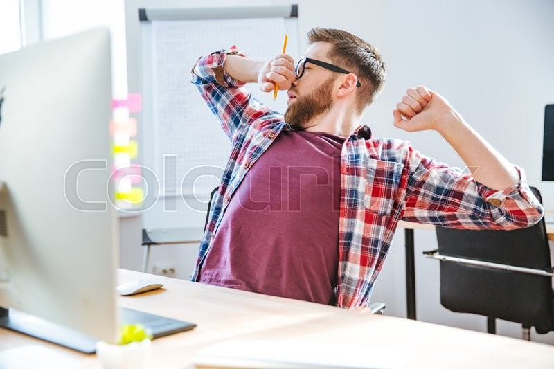 Stock image of 'Tired handsome young man with beard in glasses stretching and yawning on workplace'