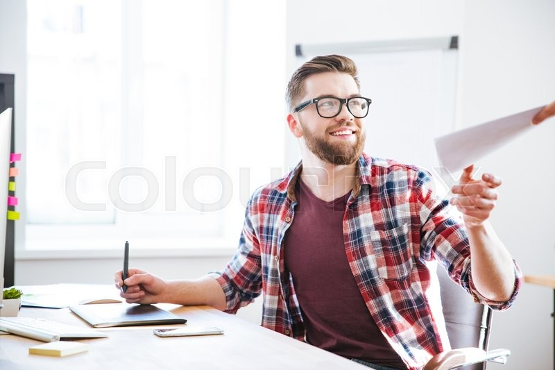 Stock image of 'Happy handsome bearded designer using graphic pen tablet with stylus and receiving blueprints'
