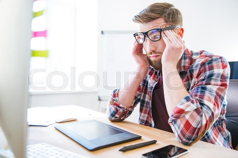 Stock image of 'Tired exhausted young man with beard in glasses sitting on workplace and touching temples'