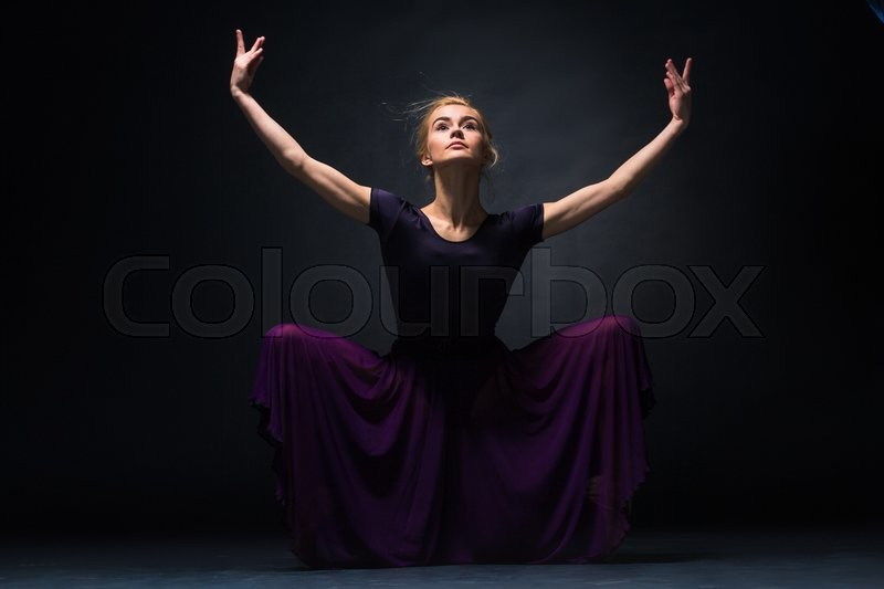 Stock image of 'young beautiful modern style dancer posing on a studio dark background'
