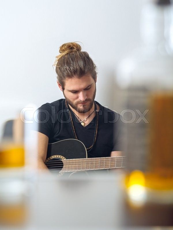 Stock image of 'Photo of a male songwriter with acoustic guitar taken between a blurred whisky bottle and rocks glass.'