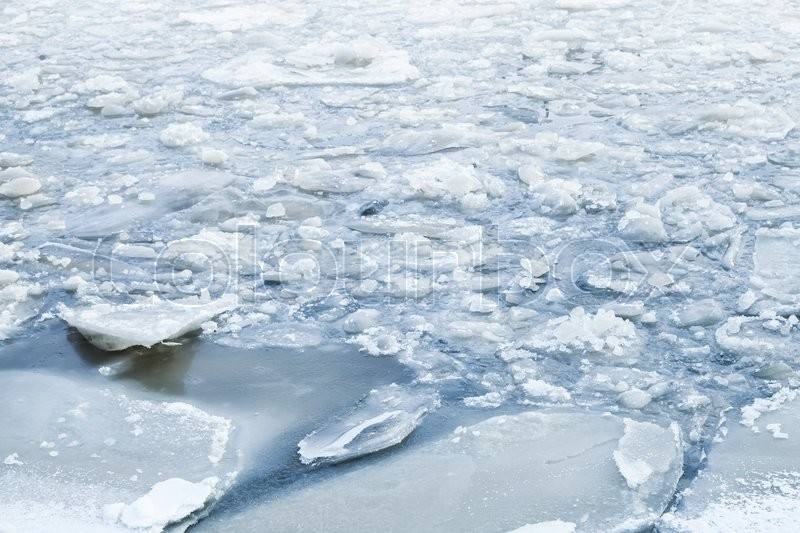 Stock image of 'Ice fragments covered with show on cold river water. Dark blue natural winter background'