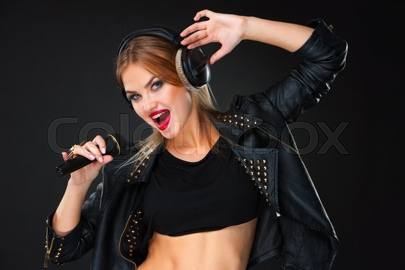 Stock image of 'Portrait of a beautiful blonde young woman singing into microphone with headphones in studio on black background'