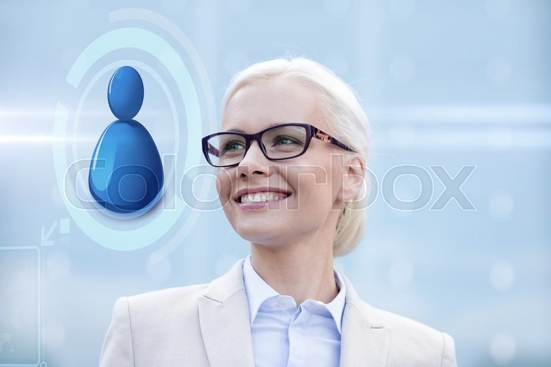 Stock image of 'business, people, technology and communication concept - young smiling businesswoman in eyeglasses and virtual screen with user icon outdoors'