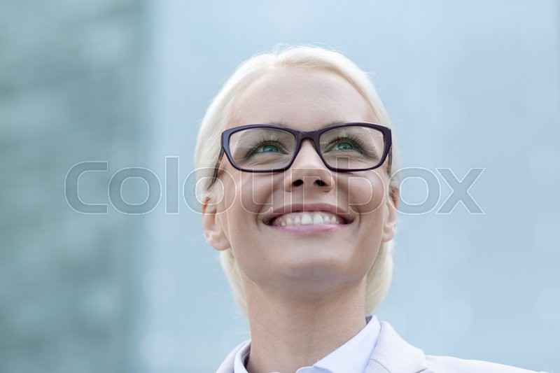Stock image of 'business, people and education concept - young smiling businesswoman over office building'