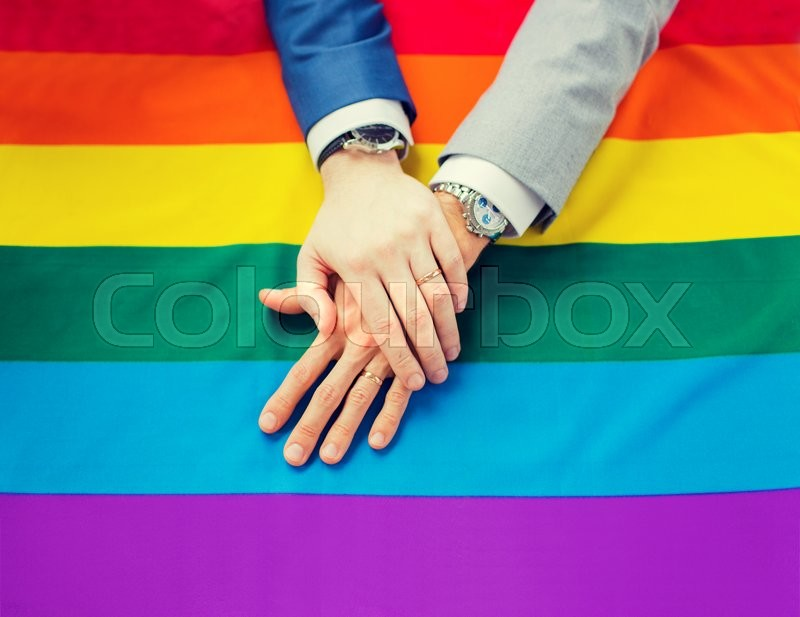 Stock image of 'people, homosexuality, same-sex marriage, gay and love concept - close up of happy male gay couple hands over rainbow flag'