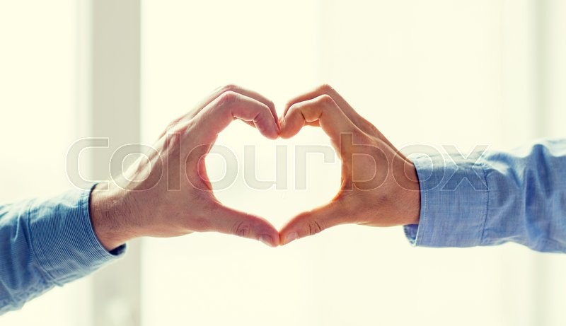 Stock image of 'people, homosexuality, same-sex marriage, gesture and love concept - close up of happy male gay couple hands showing heart hand sign'